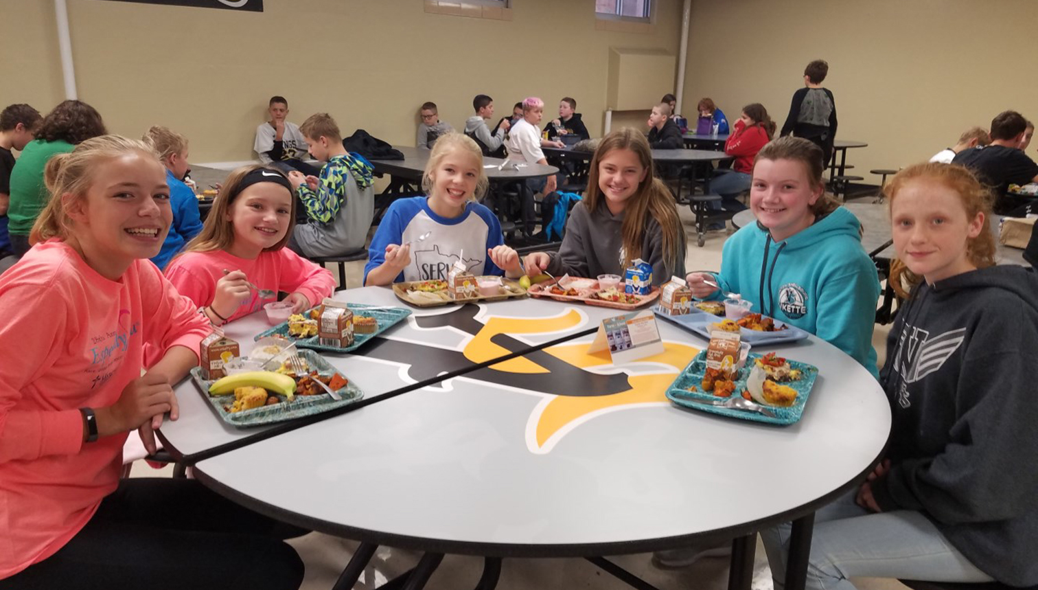 Girls sitting around lunch table in the Vinton-Shellsburg Middle School lunch room.
