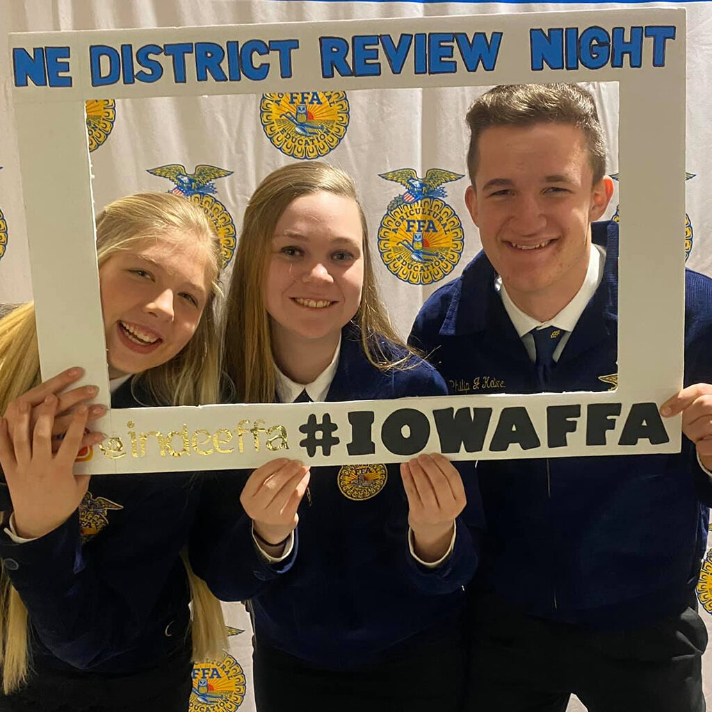 Two female students and a male student wearing FFA jackets hold a cardboard photo frame.