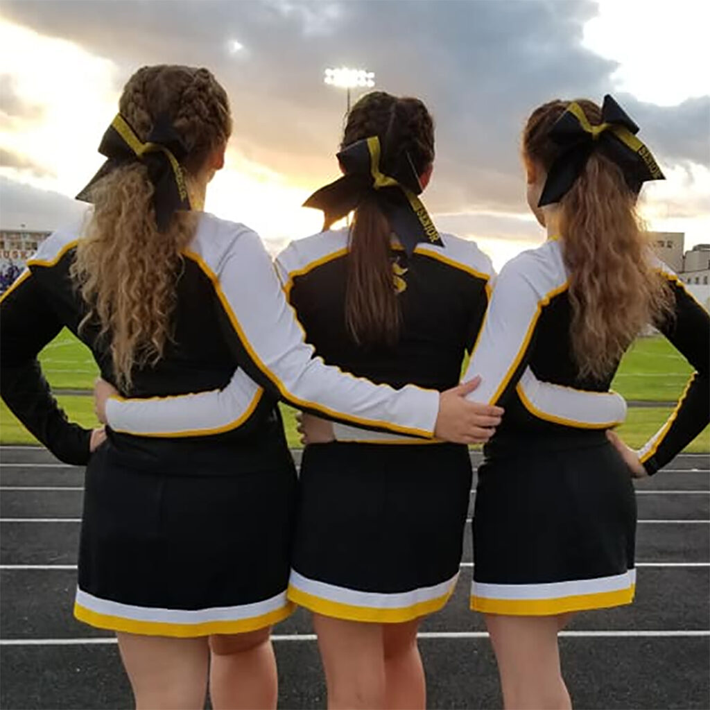 Three girls in cheerleader uniforms link arms and face away from the camera.