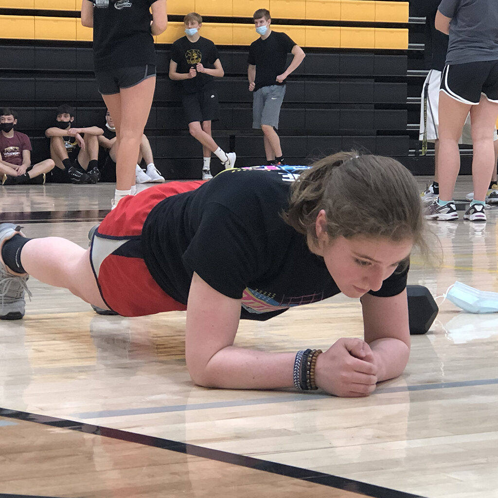Female high school student holds a plank position in the high school gym