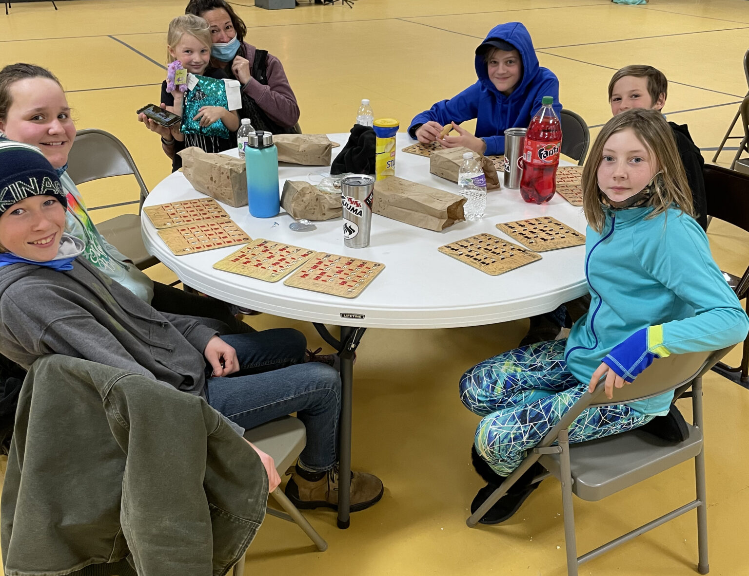 A group of home school students sit at a round table playing bingo at the Vinton Skate and Activity Center.