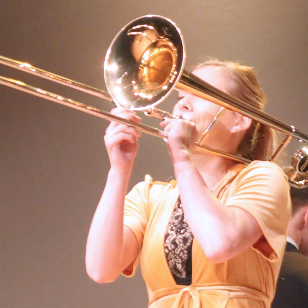 Female high school student playing a trombone at a jazz concert.
