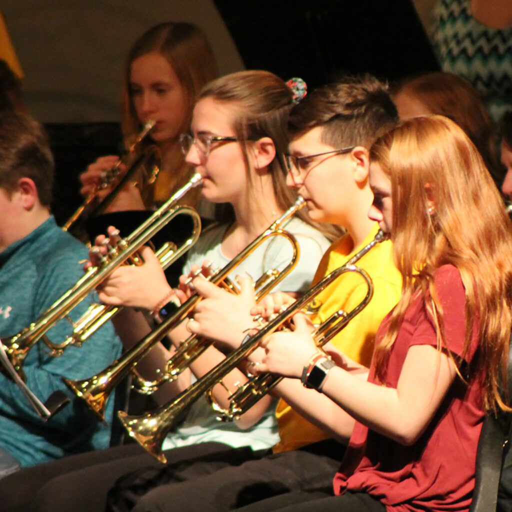 Middle school students all playing trumpets sit together at a band concert