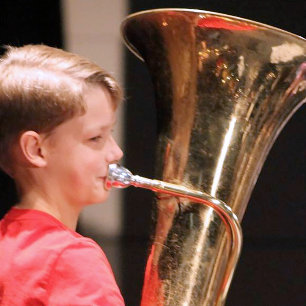 Male middle school student plays the tuba at a band concert.