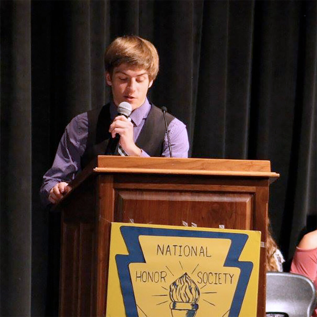 Male high school student standing behind a podium at a National Honor Society event.