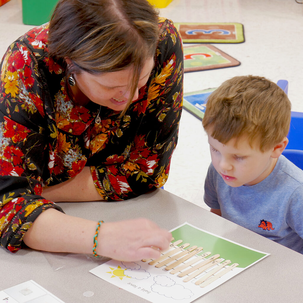 Female teacher sitting with pre-school boy.