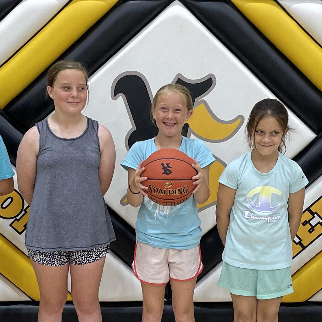 Three girls standing side-by-side in Shellburg Gym