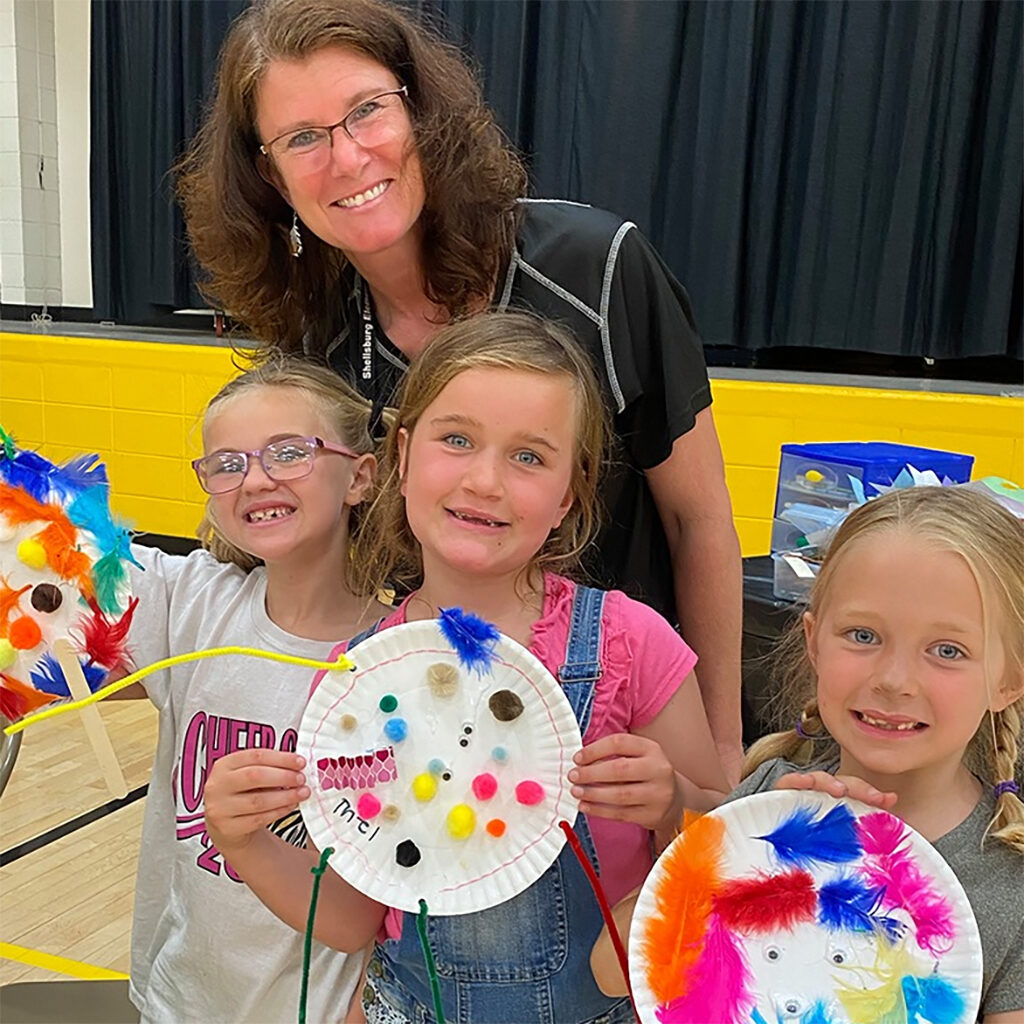 Female teacher with three students holding paper plate craft projects.