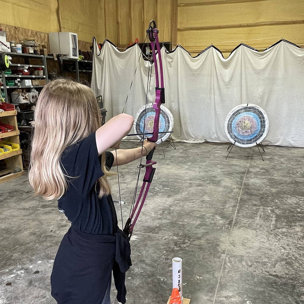 Female elementary student aiming bow and arrow at an indoor target range.