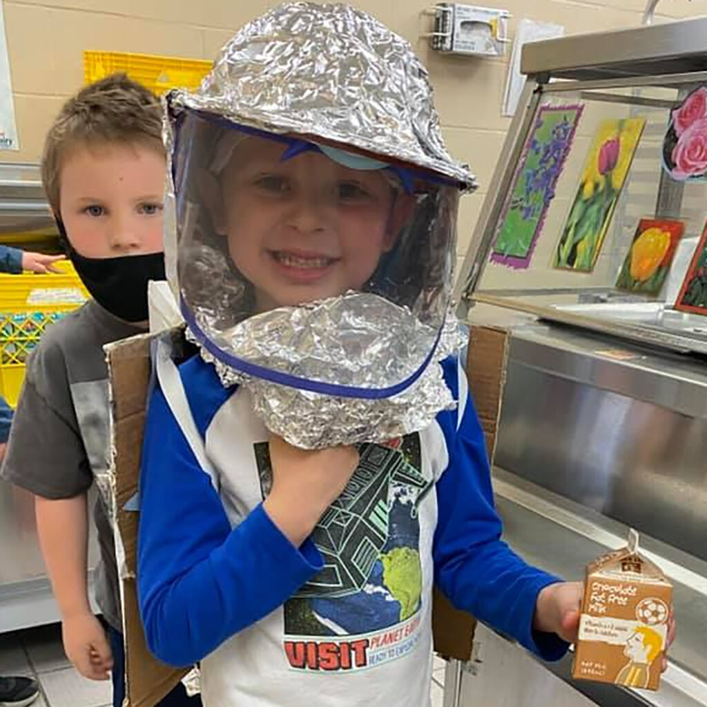 Pre-school student holding small cartono of milk wearing a face mask made of aluminum foil