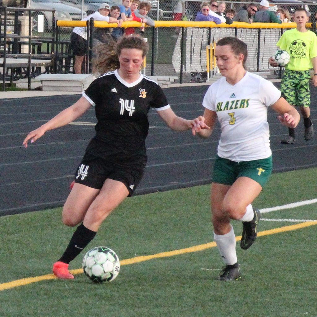 A Vikette soccer player dribbles the ball down the field.