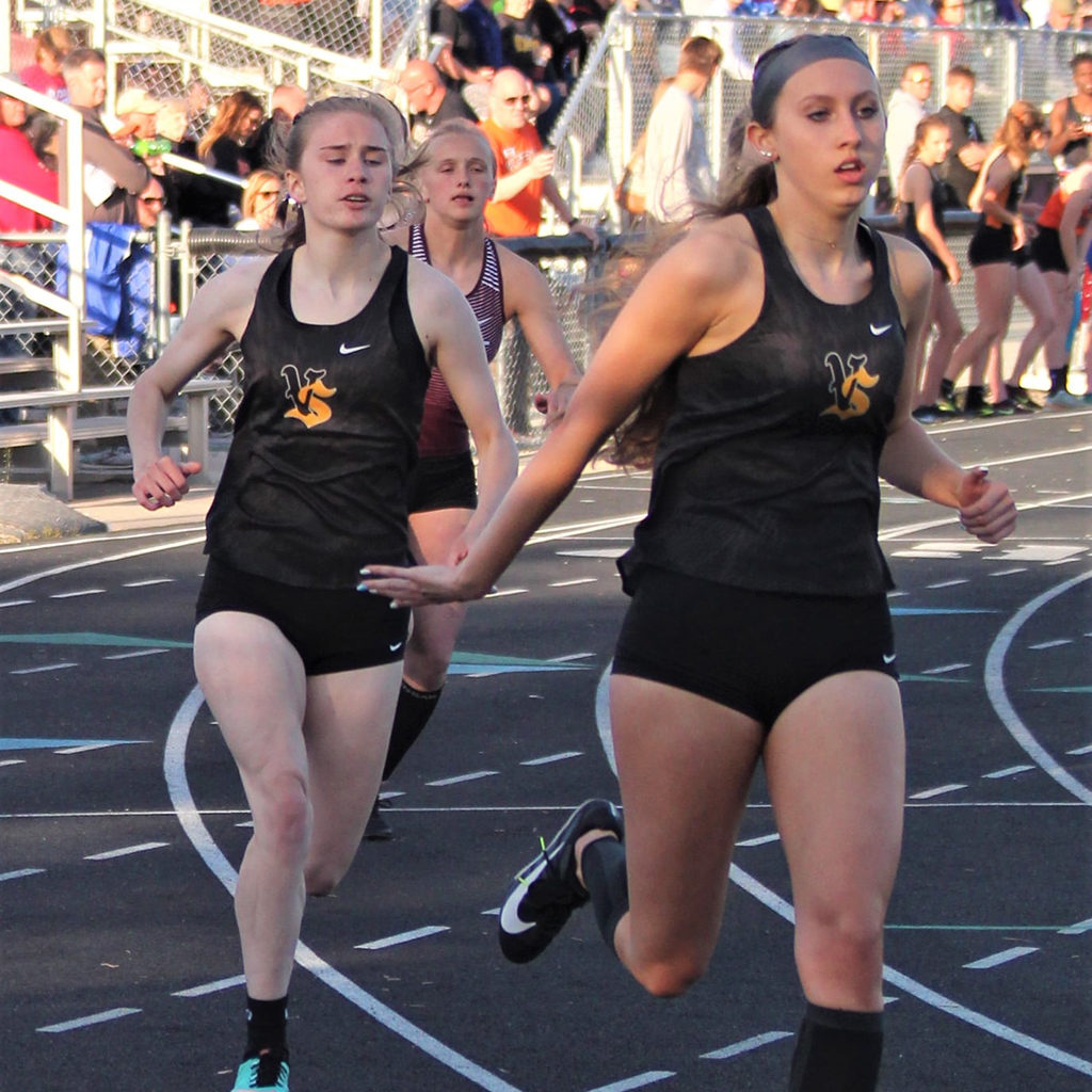 Two Vikette track team members pass the baton in a relay race.