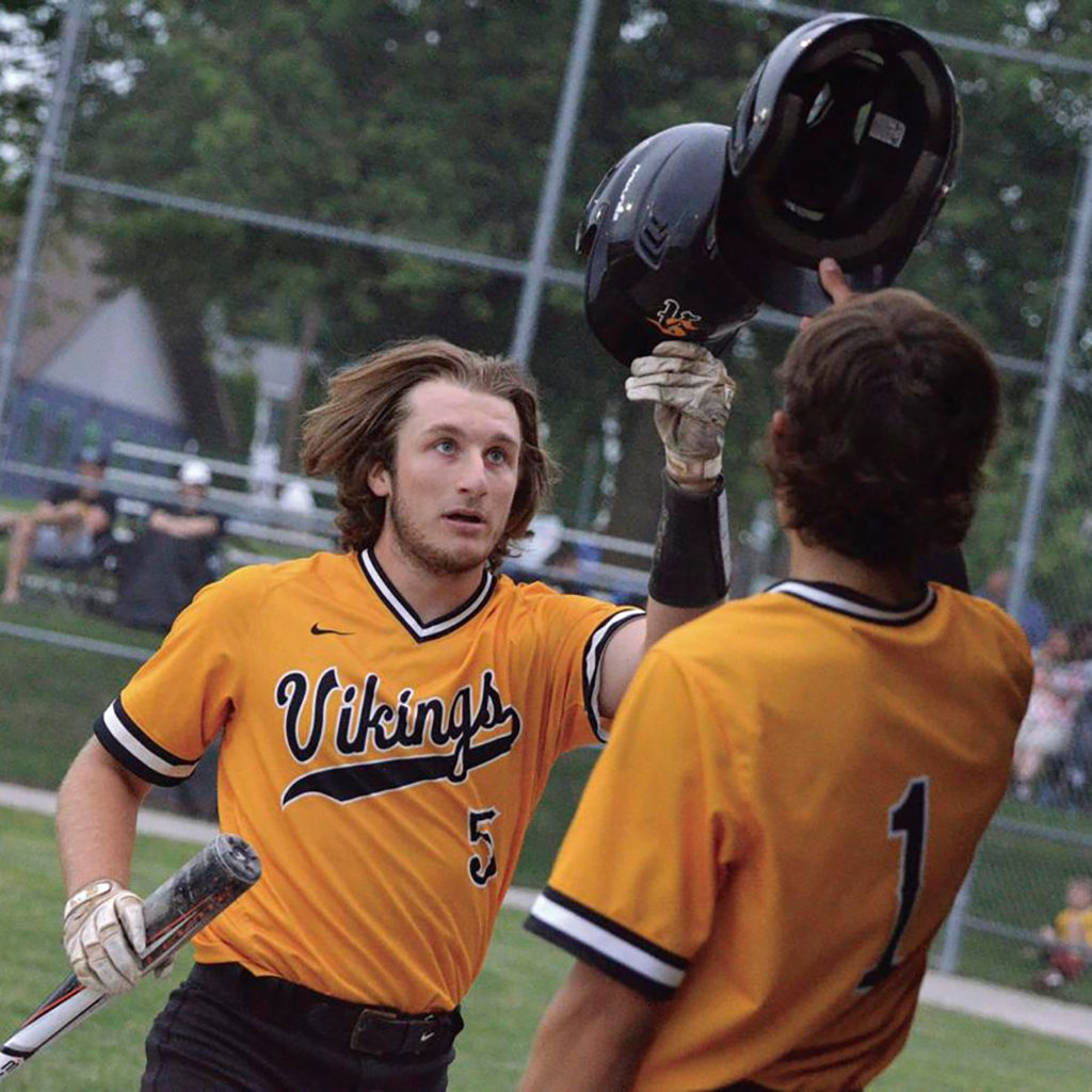 Two Viking baseball players tap their helmets together.
